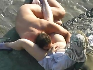 Adult husband and wife having sex on the beach.